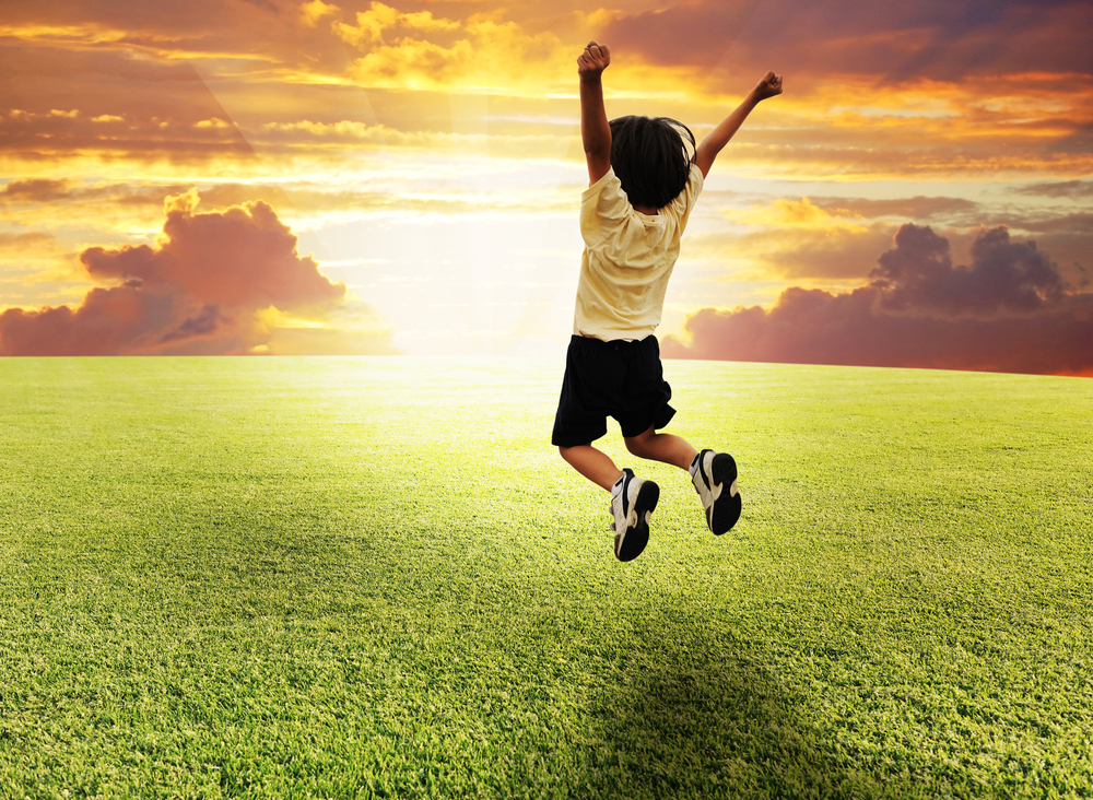 Happy successful winner child jumping on a beautiful green meadow