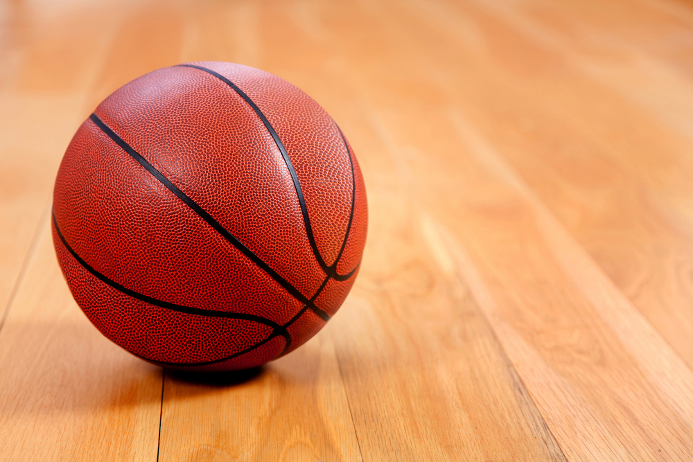 Image of a basketball lying on a wooden floor